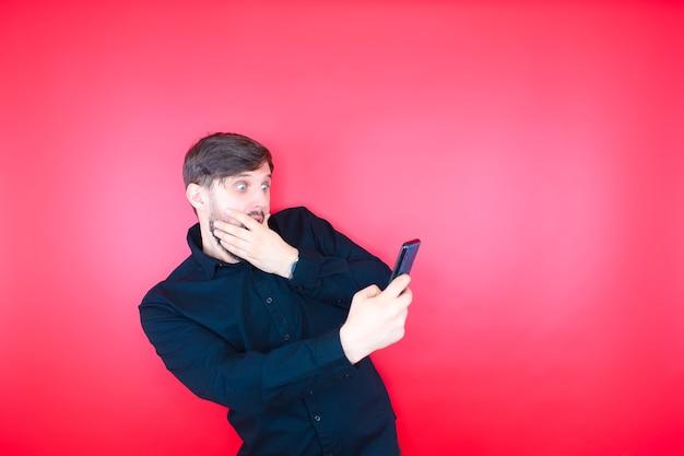 黒いシャツを着たあごひげを生やした男が驚いて電話の画面を見る
