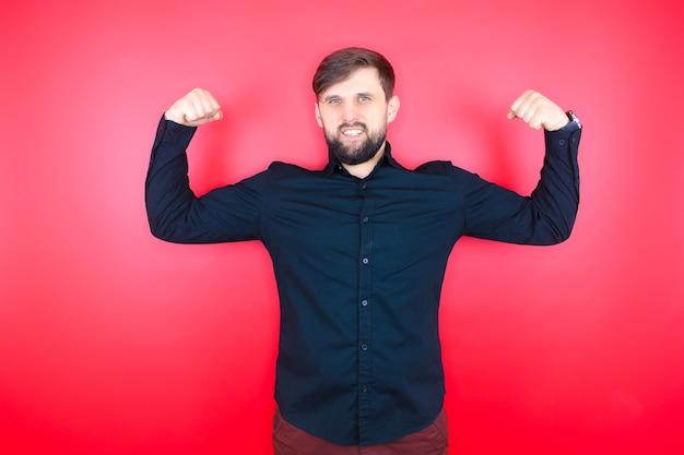 黒のシャツを着たあごひげを生やした男が筋肉を見せびらかす