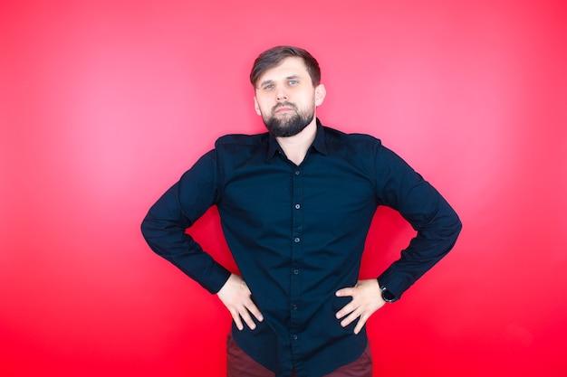 黒のシャツを着たひげを生やした男が赤い背景の上に立ってポーズをとる