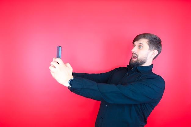黒いシャツを着たあごひげを生やした男が、電話の画面をじっと見つめています。