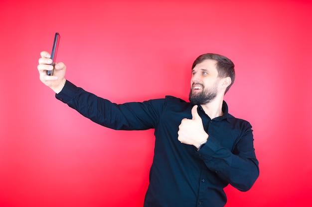 黒のシャツを着たあごひげを生やした男性が携帯電話で自分撮り写真を撮ります。赤い背景のひげを生やしたブロガー