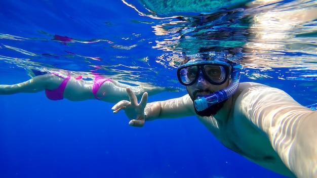 マスクと呼吸管のひげを生やした男は、彼の後ろを泳いでいる女の子を背景に紅海に飛び込みます