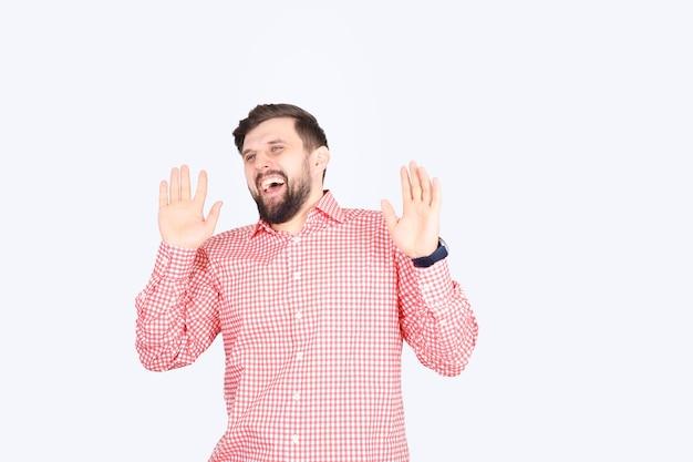 분홍색 체크 셔츠를 입은 수염 난 남자가 웃는다. 젊은 형태가 이루어지지 않은 남자 재미