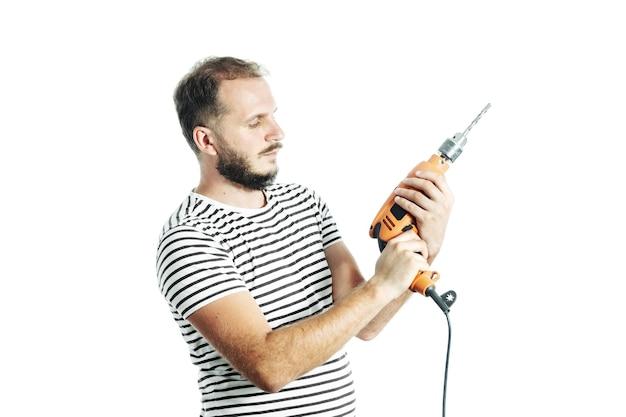 縞模様のtシャツを着たひげを生やした男性が、疑わしい表情で電気ドリルを手に持っています