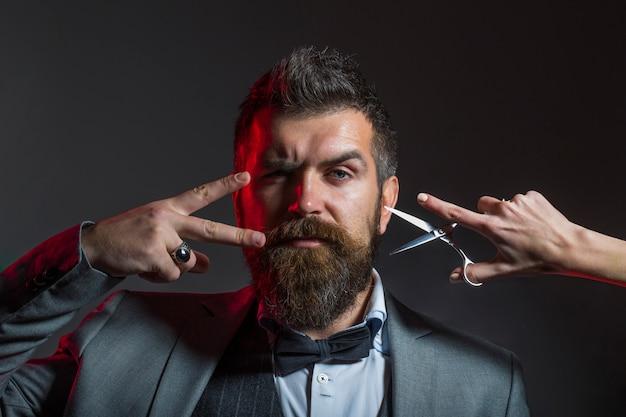 Бородатый мужчина в костюме держит ножницы.