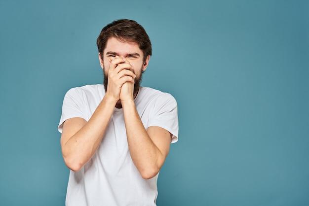 彼の手の感情青い背景で白いtシャツのジェスチャーでひげを生やした男