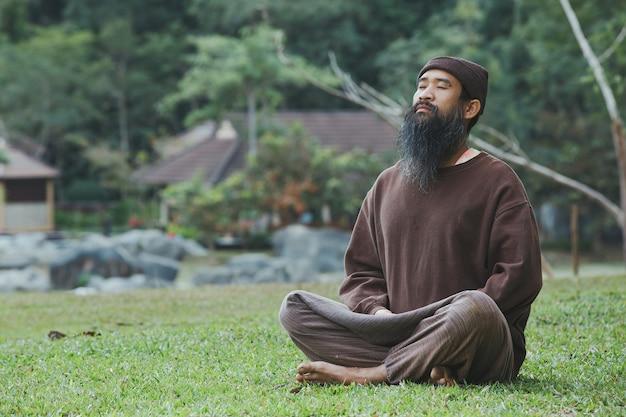 수염 난된 남자가 푸른 잔디에 명상을