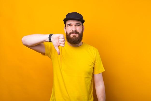 수염 난 남자가 불안한 노란색 벽 근처에서 싫어하는 표시를 보이고있다