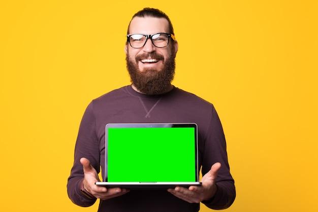Бородатый мужчина улыбается и в очках держит компьютер