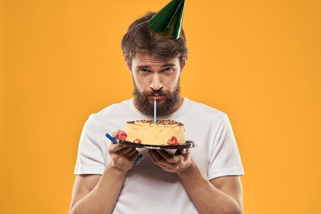 ケーキと帽子をかぶったひげを生やした男が悲しい間彼の誕生日を祝う