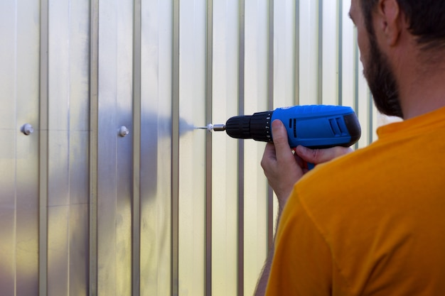 Бородатый мужчина с отверткой в руке прикрутил винты к листам металлического профиля