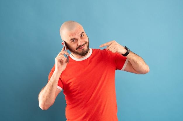 파란색 바탕에 빨간색 티셔츠를 입은 수염 난 중년 남자가 전화를 손으로 가리 킵니다. 전화하세요. 외딴.