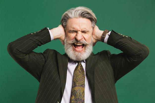 スーツを着たひげを生やした中年教師がストレスを感じ、手で耳を閉じ、緑の壁に怒りで叫びます。