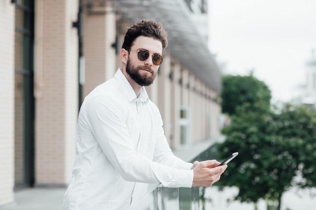 흰색 셔츠와 선글라스를 쓴 수염을 기른 진지하고 세련된 남자가 휴대전화를 들고 현대적인 사무실 근처의 거리에 서 있다