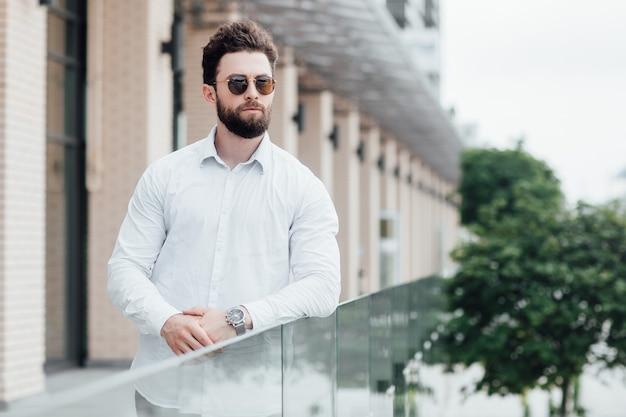 흰색 셔츠와 선글라스를 쓴 수염이 있고 진지하고 세련된 남자가 현대 사무실 근처 도시의 거리에 서 있습니다.