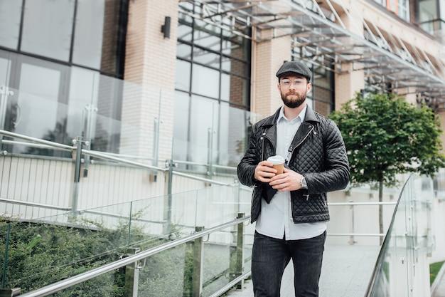 수염이 있고 진지하고 세련된 남자가 현대적인 사무실 센터 근처의 도시 거리를 걷고 손에 커피를 들고 있습니다.