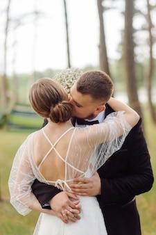 Бородатый, стильный жених в костюме и красивая блондинка невеста в белом платье с букетом в руках стоят и обнимаются на природе в сосновом лесу.