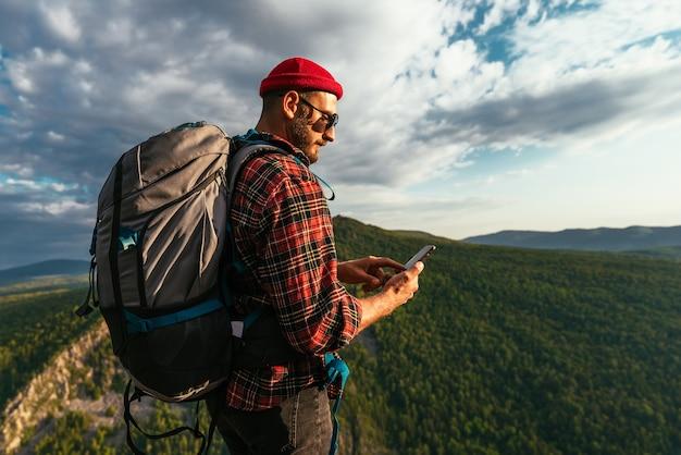 Бородатый путешественник с рюкзаком на вершине горы. портрет путешественника в красной кепке и солнечных очках. турист с рюкзаком стоит на фоне горы. копировать пространство