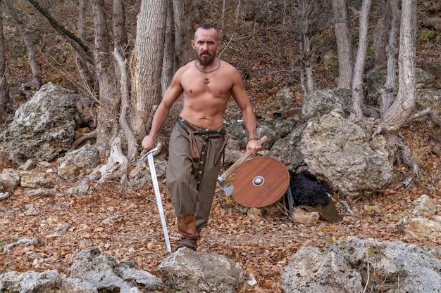 Бородатый викинг с обнаженным торсом держит в одной руке меч, а в другой - боевой топор.