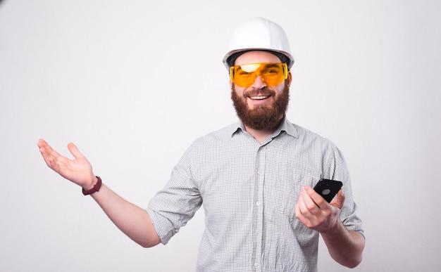 수염 난 젊은 엔지니어가 스마트 폰을 들고 카메라에 웃고 흰 벽 근처에 헬멧과 보호 안경을 쓰고 있습니다.