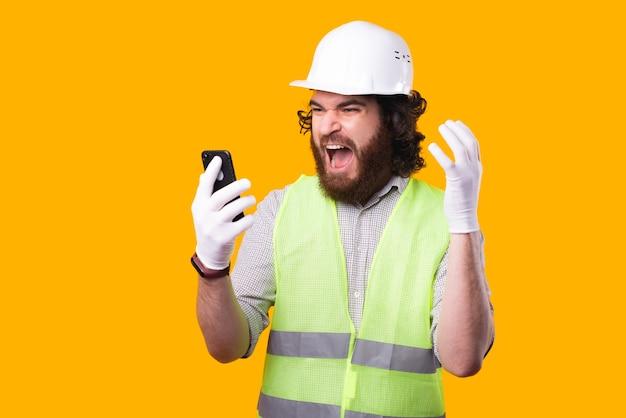 수염 난 젊은 엔지니어가 노란색 벽 근처에서 자신의 휴대 전화를보고 충격을 받고 있습니다.