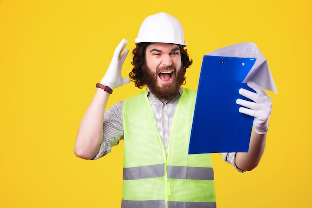수염을 기른 젊은 엔지니어가 노란색 벽 근처에서 그의 작업 pappers에서 스트레스를 찾고 있습니다.
