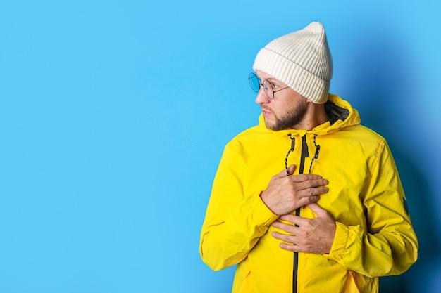 両手で胸を抱えているひげを生やした若い男は、青い背景を見下ろします。