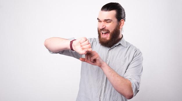 あごひげを生やした若い男は、彼が白い壁の近くで遅れていることを恐れて彼の時計にストレスを感じている