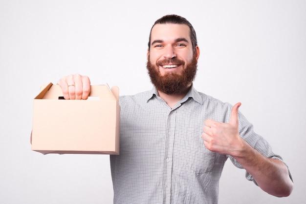 Бородатый молодой человек улыбается в камеру и, показывая большой палец вверх, держит коробку для доставки