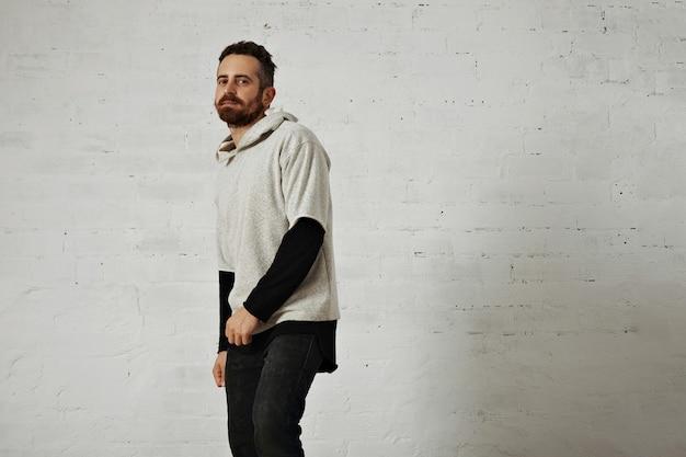 Бородатый молодой человек представляет простой серый свитер из мягкого хлопка с черными джинсами, изолированными на белом
