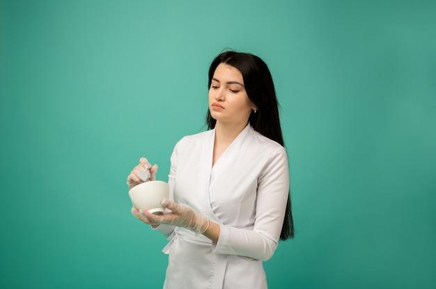 Косметолог в белом медицинском костюме помешивает в чашке кисточкой на бирюзовом