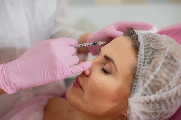 미용사는 보톡스를 환자의 이마의 안면 근육에 주사합니다.