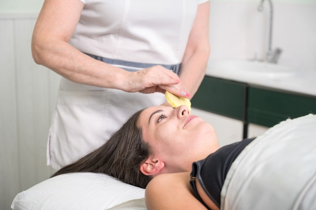 Косметолог выполняет снятие макияжа с лица клиентки в салоне красоты.