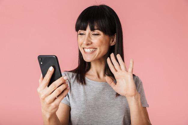 手を振って話している携帯電話を使用して淡いピンクの壁の壁の上に孤立してポーズをとってポーズをとる美しい驚くべき興奮した幸せな女性。