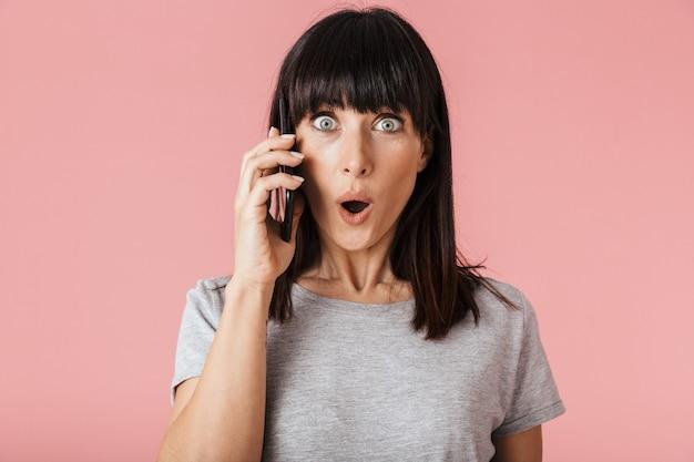 携帯電話で話している淡いピンクの壁の壁の上に孤立してポーズをとってポーズをとる美しい驚くべき興奮したショックを受けた女性。