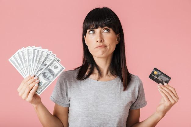 お金とクレジットカードを保持している淡いピンクの壁の壁の上に孤立してポーズをとる美しい驚くべき思考の女性。