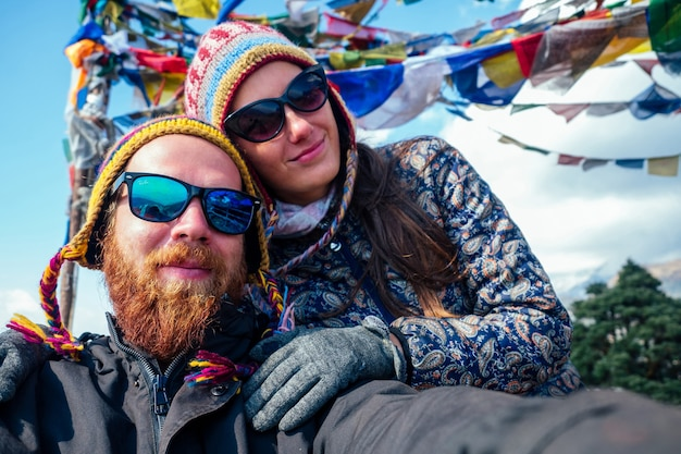 美しくアクティブな女性とあごひげを生やした男性が山でのトレッキングで自分撮りをします。山でのアクティブなレクリエーションと観光の概念。ネパールヒマラヤでのトレッキング