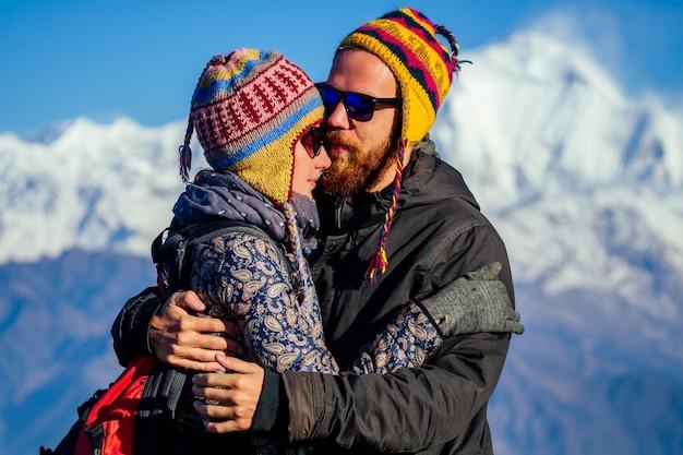美しくアクティブな女性と男性が山を背景に抱きしめています。山でのアクティブなレクリエーションと観光の概念。ネパールヒマラヤでの愛のトレッキングのカップル。