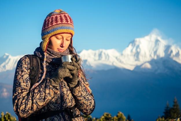 아름답고 활동적인 여성이 손에 뜨거운 음료를 들고 컵을 들고 있습니다. 산에서의 활동적인 레크리에이션과 관광의 개념. 네팔 히말라야 트레킹.