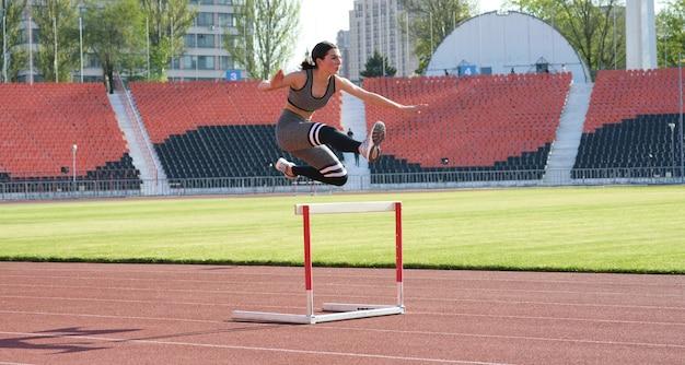 아름답고 운동 선수가 경기장에서 장애물을 실행하고 있습니다.