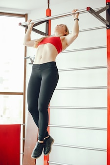 A beautiful and athletic sportswear girl training in the gym