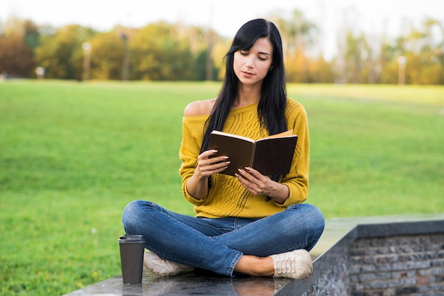 Красивая и привлекательная кавказская девушка брюнетка в желтом свитере читает книгу, сидя в парке.