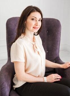 Красивая и милая брюнетка в легкой блузке сидит в кресле, улыбается и смотрит в камеру.