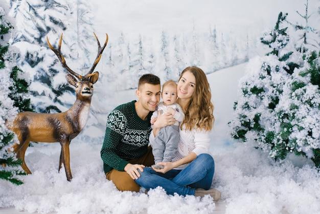 Красивая и счастливая семья молодых родителей и ребенка в зимних свитерах в фальшивом зимнем лесу, в фотозоне в студии