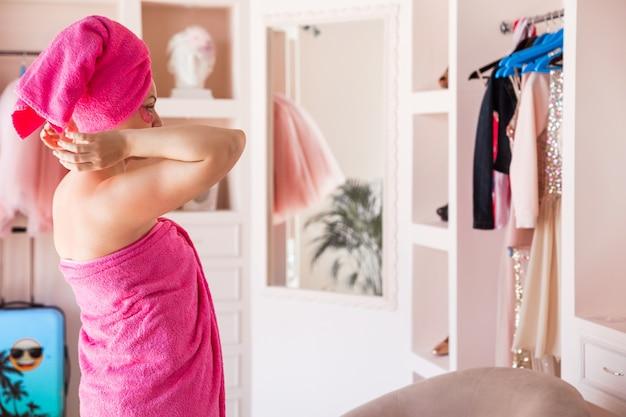 Красивая и счастливая женщина с телом и волосами, завернутыми в розовое полотенце и с розовыми пятнами под глазами, позирует в спальне.
