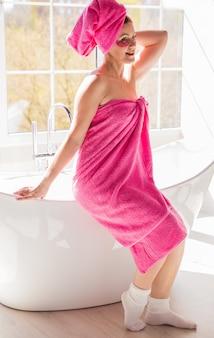 Красивая и счастливая женщина с телом и волосами, завернутыми в розовое полотенце, и с розовыми пятнами под глазами.