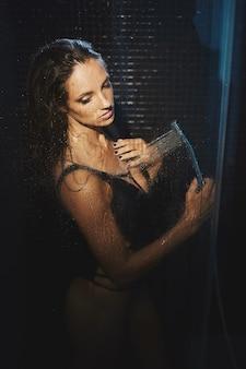 Красивая и стройная молодая женщина принимает душ очаровательная девушка в бикини позирует в душевой кабине