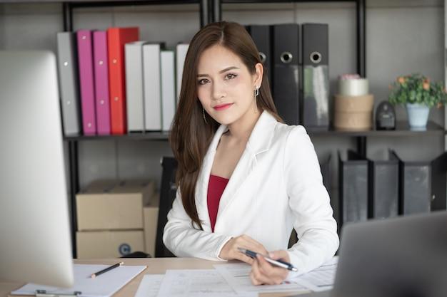 Красивая и умная работающая женщина сидит за партой в офисе.