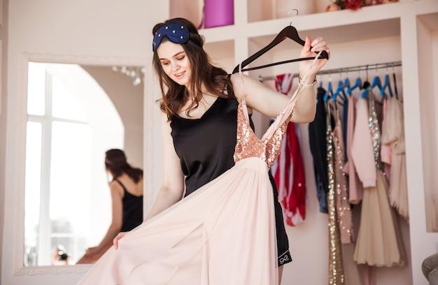 Красивая и стильная брюнетка в черном пиджаке выбирает платье и свой гардероб. девушка держит в руках платье и смотрит на него.