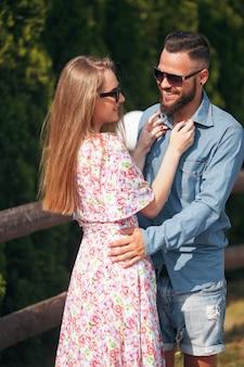 ブロンドの髪、薄いドレス、花束を持つ美しく、優しい女の子は、青いシャツとショートパンツを着たハンサムなボーイフレンドと一緒に日当たりの良い公園を歩きます。晴れた日。夏。